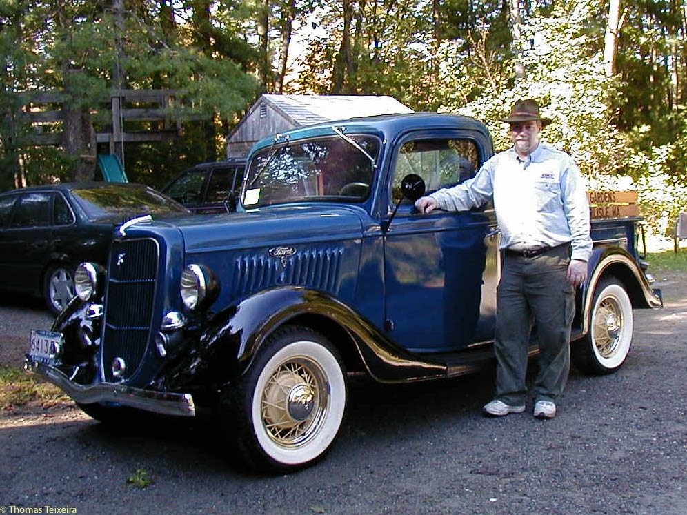 The author standing beside blue 1935 Ford Pickup with black fenders and white wall tires