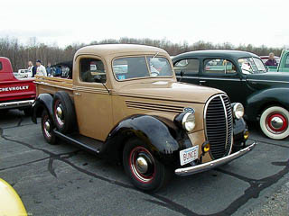 1938 Ford pickup truck. Tan body with black fenders.