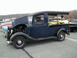 1936 farm truck. The cab roof extends over the truck bed but the back and sides above the bed are open.