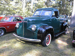 Green Studebaker pickup truck with black fenders